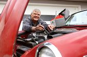 foto of senior men  - Senior man working on classic car - JPG