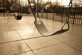 picture of obese children  - Swings at an empty playground signifying lost youth or lost generation - JPG