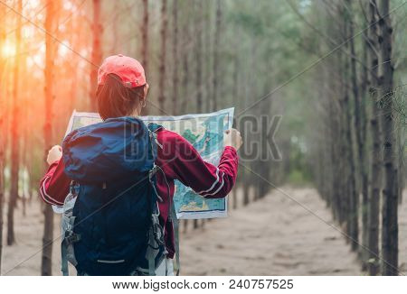poster of Asian Woman Travel With Backpack At Spruce Forest Looking Map The Route Go To Destinations, Girl Tra