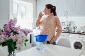Woman Drinking Filtered Water From Filter Jug In Kitchen. Modern Kitchen Design. Healthy Lifestyle C poster