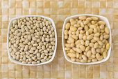 Soaked and dried white pea beans, Navy bean, Pearl Haricot, Boston bean in white bowl on yellow cera poster