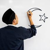 Young Muslim man drawing a muslim crescent and a star on a whiteboard poster