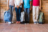 Low section of elementary students standing outside class with backpacks. Legs of four boys and girl poster