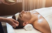 Man Getting Facial Nourishing Mask By Beautician At Spa Salon, Closeup. Apply Face Mask, Spa Beauty  poster