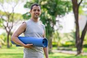 Positive Indian Guy With Yoga Mat Getting Ready For Outdoor Class. Young Man In Sportswear Finishing poster