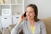 people, technology and communication concept - happy middle-aged woman calling on smartphone at home poster