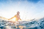 Surfer haves fun and makes water splashes being on line up during sunrise surf session. poster
