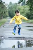 A Wet Child Is Jumping In A Puddle. Fun On The Street. Tempering In Summer poster