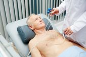 Serious calm elderly patient lying on table while unrecognizable doctor in lab coat preparing him fo poster
