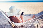 Vacation And Technology. Young Pretty Woman In Hat And Swimsuit Using Smartphone Laying In Hammock O poster