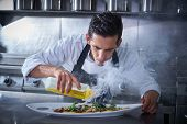 Chef preparing octopus recipe in kitchen with smoke and oil poster