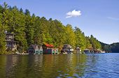 stock photo of taper  - The shoreline of a lake with mountain and houses tapering down under a blue sky - JPG