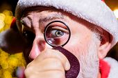 Santa Looks Through Lens. Santa Claus Looking Through Magnifying Glass At Christmas. Bearded Santa L poster