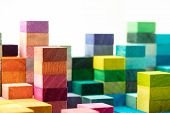 The building blocks. Spectrum of stacked multi-colored wooden blocks with white space above. Backgro poster