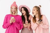 Image of positive young girls wearing pink clothes smiling and peeking in friends cellphones isolat poster