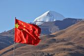 Постер, плакат: Святая гора Кайлаш в Тибете и китайский флаг на переднем плане