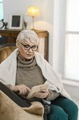 Thougtful Old Lady In Glasses Is Relaxing At Her Comfortable Flat. She Is Sitting On The Leather Arm poster