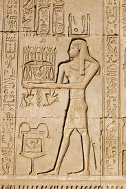 image of life after death  - Ancient Egyptian bas relief carving of a priest making an offering to the god Ka.  Ka is a complex yet vital figure in the belief of life after death.  Outer wall of Dendera Temple near Qena, Egypt.
