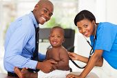 pretty african female nurse examining little boy with male doctor