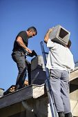 picture of top-less  - Two roofers hard at work - JPG