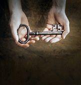 image of skeleton key  - Man holding a big old antique skeleton key in his hands - JPG