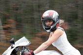 picture of crotch-rocket  - A pretty blonde girl in action driving a motorcycle at highway speeds.