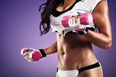 pic of flat stomach  - Woman with flat and sexy stomach working out with a dumbbell - JPG