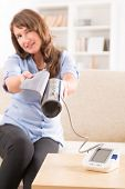 Beautiful woman checking her blood pressure at home and presenting pressure monitor cuff