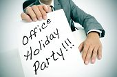 picture of office party  - a man wearing a suit sitting in a desk holding a signboard with the text office holiday party written in it - JPG