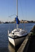 picture of sloop  - The Baltimore Maryland skyline in visible through the rigging of a small cruising sloop - JPG