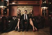 Handsome brunette wearing suit sitting on sofa with two beautiful women