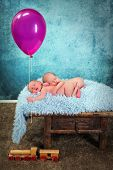 Adorable newborn twin babies asleep and holding a pink balloon
