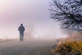stock photo of walking away  - A person walk into the misty foggy road in a dramatic sunrise scene with abstract colors - JPG