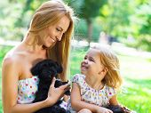 picture of puppies mother dog  - Cute little girl and her mother hugging dog puppies - JPG