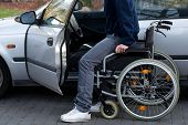 stock photo of driveway  - Disabled driver getting into a car at driveway - JPG