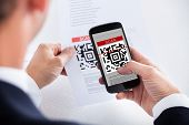 stock photo of barcode  - Close-up Of Businessman Scanning A Barcode Using Cell Phone ** Note: Shallow depth of field - JPG