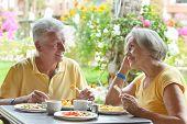 picture of elderly  - Cute elder couple eating breakfast  in summer outdoors - JPG