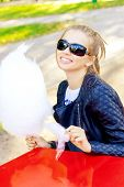 foto of candy cotton  - beautiful happy smiling girl in sun glasses eating cotton candy at a table in the Park on a Sunny day - JPG