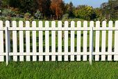picture of grass area  - White fence on green grass against garden - JPG