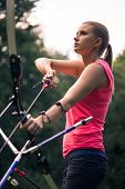 stock photo of longbow  - Selective focus on the bow which is pulled at something by lovely young fair - JPG