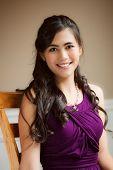 pic of biracial  - Beautiful biracial young woman in purple dress relaxing in chair  - JPG