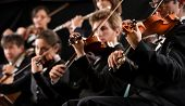 pic of orchestra  - Symphony orchestra first violin section performing on dark background - JPG