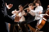 stock photo of orchestra  - Conductor directing symphony orchestra with performers on background hands close - JPG