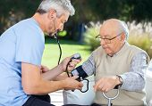 pic of nursing  - Male doctor measuring blood pressure of senior man at nursing home - JPG