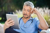 picture of male nurses  - Male doctor using tablet PC in nursing home - JPG