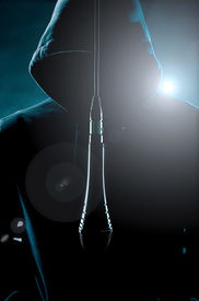 stock photo of gangsta  - image of a man wearing a hoody with microphone - JPG