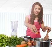 image of wifes  - portrait young wife cooking vegetables at kitchen - JPG