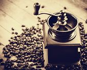 stock photo of threshing  - Coffee grinder with coffee grains on a wooden table - JPG