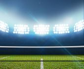 stock photo of arena  - A tennis court in an arena with a marked green lawn surface at night under illuminated floodlights - JPG