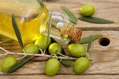 pic of olive branch  - olive oil with branch of olive tree placed on wooden background - JPG